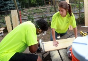 Stephanie Buda shows a student how to use a power saw